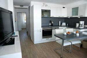 Küchenzeile mit Essplatz und Schlafzimmer im Hintergrund.